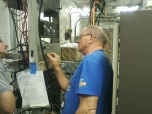 Here is Greg N0GR turning a knob. The Henry amp is the device with the dual fans near Greg's forehead. -wa0zqg
